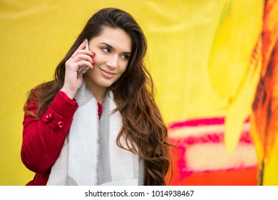 Young charming woman calling with cell telephone, attractive female with cute smile having talking conversation with mobile phone