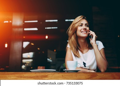 Young charming woman calling with cell telephone while sitting alone in coffee shop during free time, attractive female with cute smile having talking conversation with mobile phone while rest in cafe