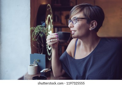 Young Charming Woman with cup of coffee, enjoying coffee break in local shop