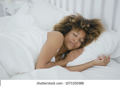 Young charming woman with curls lying in bed covered with blanket and sleeping contently having sweet dreams.