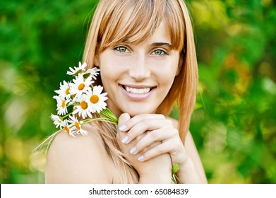 Young charming woman has control over bouquet of camomiles and smiles, against green summer nature.