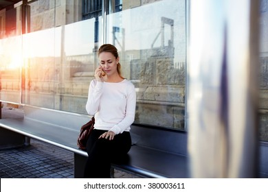 Young charming woman having bad conversation with her boyfriend while she waiting for a car on a station, attractive female calling on smart phone to her friend while sitting alone on a bus stop