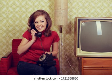 Young charming woman sitting in chair and talking on old phone in room with vintage wallpaper and retro TV set, retro stylization 60-70s 20th century. Girl in room with old fashioned interior