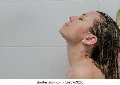 Young charming woman washes in the shower
