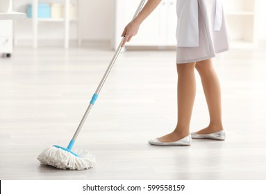Young charwoman moping floor in office, closeup