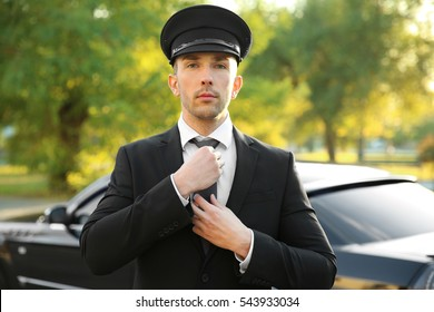 Young chauffeur adjusting tie near luxury car on the street