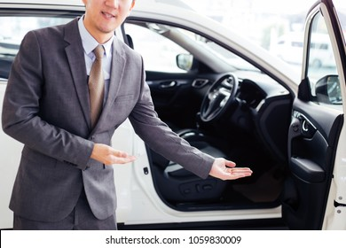 Young chauffeur in business suit welcoming rich and wealthy client on board - rich lifestyle taxi car transportation concept