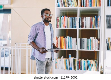 Young Cheerful African American Hipster Guy Holding Modern Portable Pc While Standing Near Bookshelf Smiling