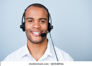 Young cheerful african guy call center worker in headset on a pure light background, wearing headset and smart white shirt, smiling