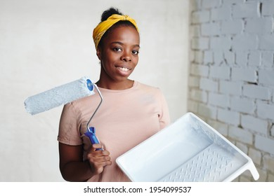 Young cheerful African woman with paintroller standing in the corner against two walls and looking at you with smile during home renovation