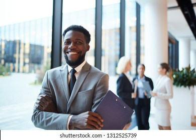 Young cheerful African-american entrepreneur or broker with toothy smile crossing his arms on chest in front of camera