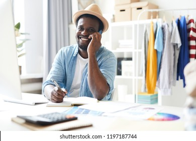 Young cheerful African-american man in smart casual looking at you while consulting someone on smartphone by workplace