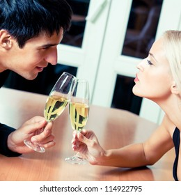 Young cheerful amorous couple with champagne on romantic date or celebrating at restaurant