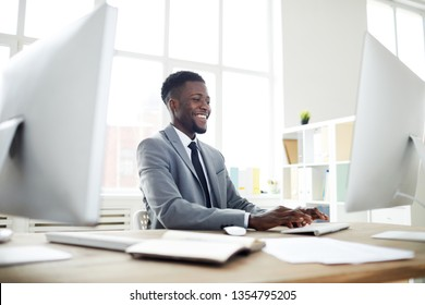 Young cheerful analyst or designer in elegant suit sitting by table in front of computer screen during work