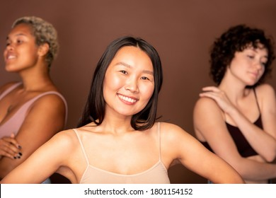 Young cheerful Asian woman in beige tanktop standing in front of two other intercultural females and looking at you with toothy smile