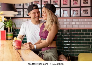 Young cheerful athletic lovers having fun at mountain hotel cafe, drinking healthy smoothie after everyday training, being in mountain vacation or holidays - Love sport and relationship concept