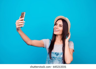 Young cheerful attractive brunette  is smiling on the blue background. She is taking selfie on the camera of her phone, wearing casual summer outfit and a hat