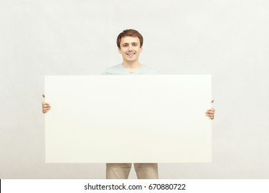 Young, cheerful attractive guy in blue t-shirt and beige shorts holding a sign isolated on white background. A place for your advertising and text.
