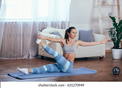 Young cheerful attractive woman practicing yoga, sitting in Sukhasana pose