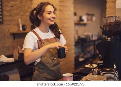 Young and cheerful barista woman make a coffee in the cafeteria