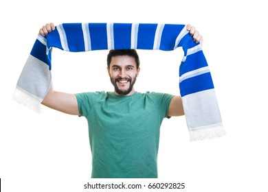 Young cheerful bearded football fan with scarf chanting with hands up
