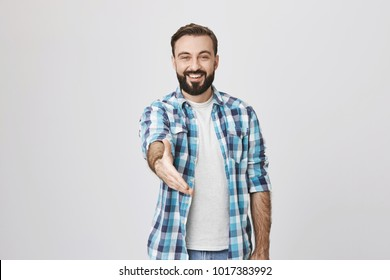 Young cheerful bearded man with trendy haircut smiling broadly while stretching hand at camera in greeting gesture, standing over gray background. Nice to meet you, I am new in this company
