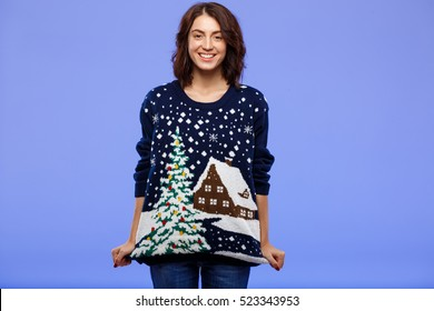 Young cheerful beautiful brunette girl in cosy knited sweater smiling posing over blue background.