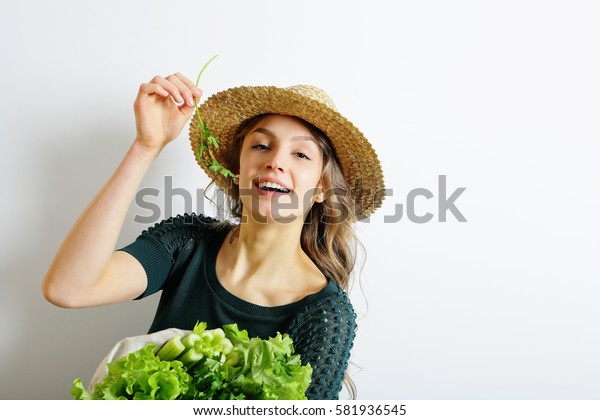 Young Cheerful beautiful woman holds parsley and herbs. Concept a healthy lifestyle