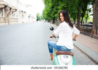 Young cheerful beautiful woman riding a scooter and looking back at camera