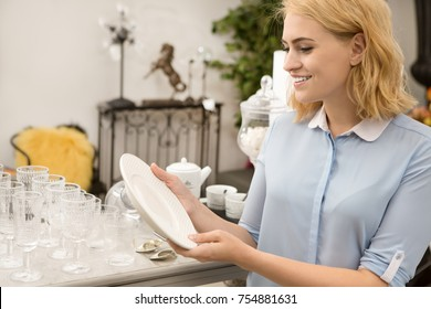 Young cheerful beautiful woman smiling while choosing dinnerware at the local store holding white plate examining it copyspace consumerism interior design home apartment houseware purchase buyer sale