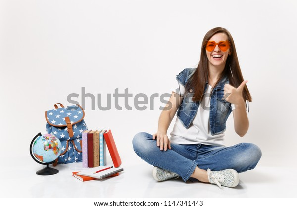 Young cheerful beautiful woman student in red heart glasses showing thumb up sitting near globe backpack school books isolated on white background. Education in high school university college concept