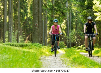 Young cheerful biker couple in woods