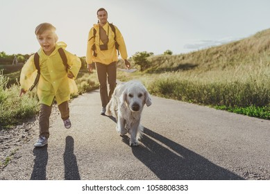 young cheerful boy with rucksack running along sunlit rode with his dog. His father walking on background. Copy space in right side. Full length portrait