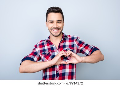 Young cheerful brunet on the pure light blue background, smiling, wearing casual outfit and gesturing a heart symbol with his hands