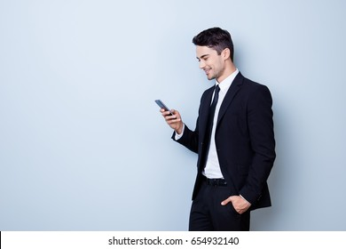 Young cheerful brunete lawyer is standing on the pure light blue background and smiling, reading good news on internet at his mobile phone, wearing suit and tie