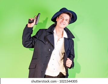 Young cheerful brunette in a dark coat. emotional portrait. image of a gangster with a gun. Desktop Wallpapers