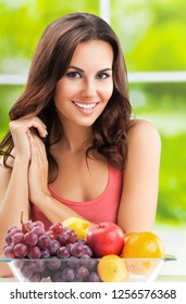 Young cheerful brunette woman with plate of fruits. Healthy eating, beauty and dieting concept.