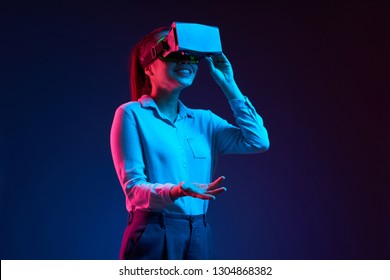 Young cheerful business lady talking when wearing virtual reality headset with application for business meetings