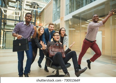 young cheerful business people in smart casual wear having fun while racing on office chairs and smiling