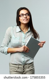 Young cheerful businesswoman holding tablet computer and looking away on gray background