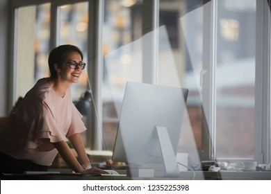 Young cheerful businesswoman leaning over table while looking at computer screen in office