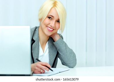 Young cheerful businesswoman signing the document in office