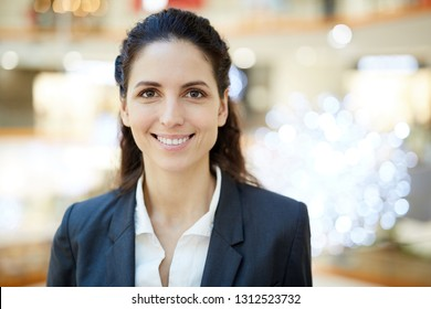 Young cheerful businesswoman with toothy smile and long dark hair looking at you while standing in front of camera