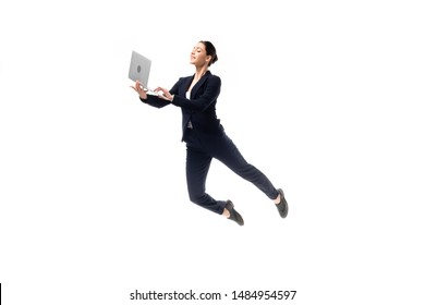 young cheerful businesswoman using laptop while levitating isolated on white