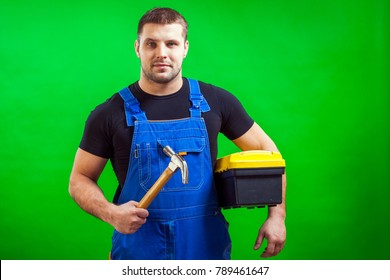 A young cheerful carpenter man in a black T-shirt and blue construction jumpsuit holds a hammer and a box with construction tools on a green isolated background
