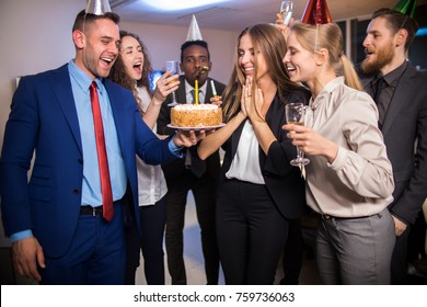 Young cheerful company workers celebrating birthday of colleague with cake and champagne in office