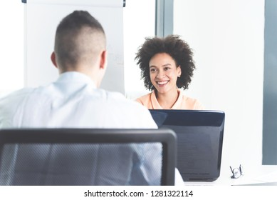 Young cheerful confident ambitious female doctor talking with her male colleague in her bright modern practice office