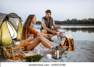 Young and cheerful couple cooking sausages at the fireplace, having a picnic at the campsite on the beach in the evening