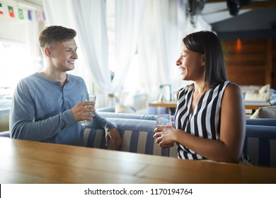 Young cheerful couple with drinks sitting by table in cafe, relaxing and enjoying their date