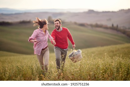 A young cheerful couple enjoying running over a large meadow while holding by hands on a beautiful sunny day. Love, relationship, together, nature